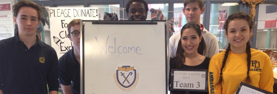 Male and female students standing beside a welcome to high school sign
