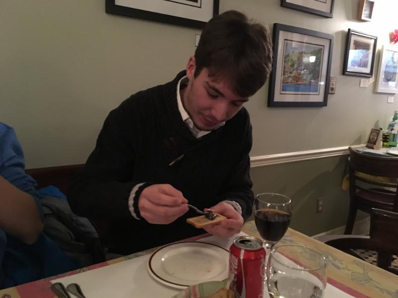 Male student trying an escargot in a restaurant.