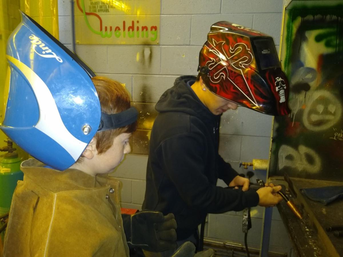 Male elementary student learns how to start a welding machine in a school's tech shop.