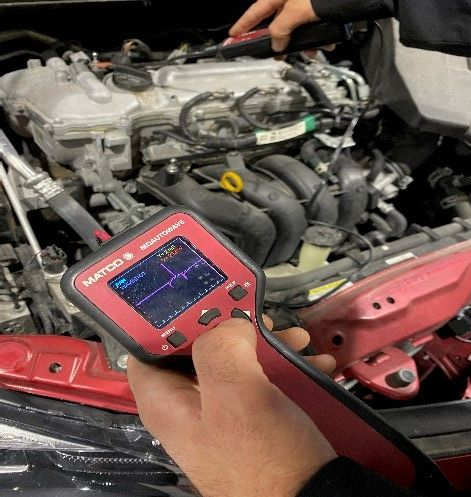 Male student holding a sensor gauge by a car engine