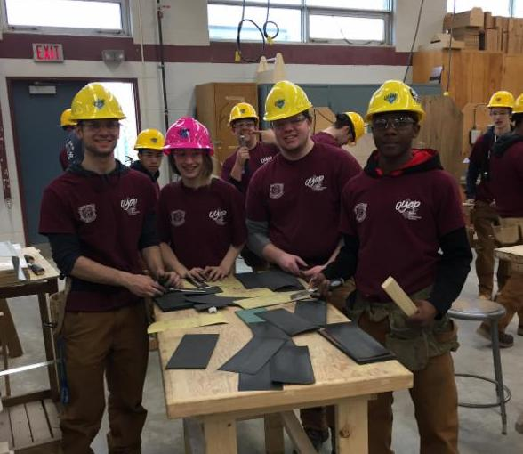 Three male students wearing yellow hard hats and one female student wearing a pink hard hat working with roofing shingles in a construction classroom.