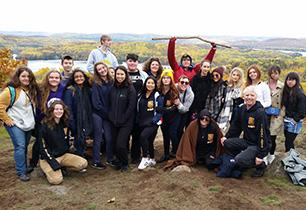 Group of female and male students pose for a picture with the fall colours in background.
