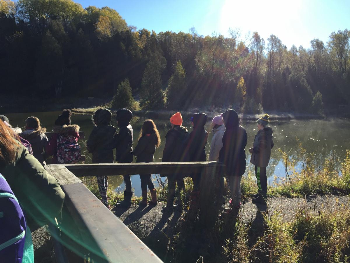 Students standing outside by a lake