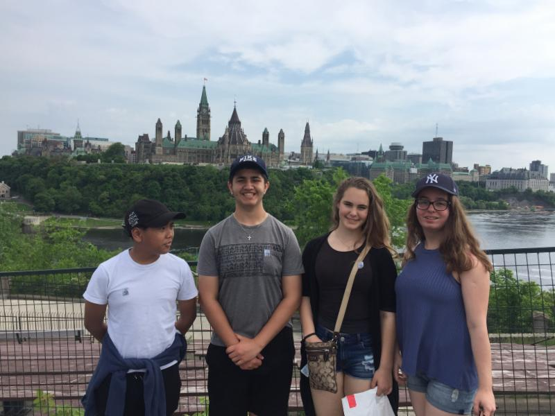 Two male and two female students standing with Parliament Hill in the background