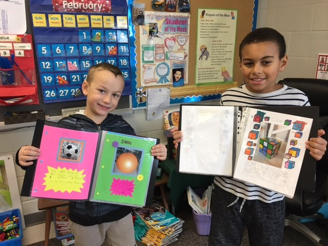 Two male students holding books with geometric shapes that they found at home and in the community