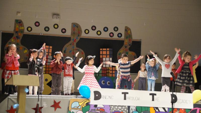 Male and female kindergarten students dancing on stage