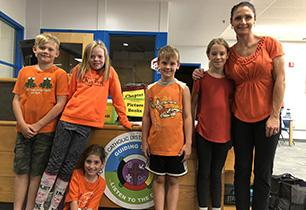Male and female students with female teacher wearing orange shirts