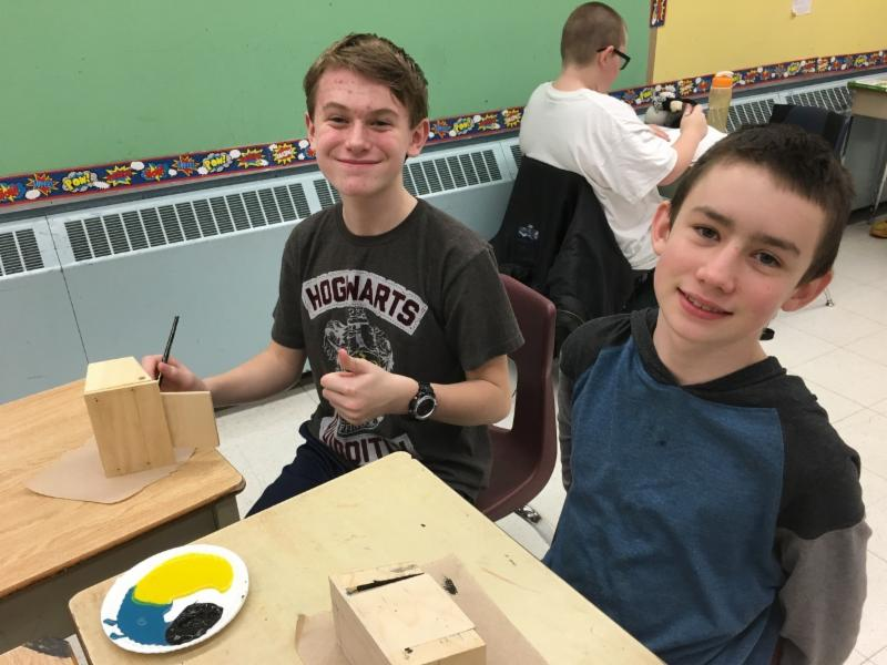 Two male student making wooden boxes in class