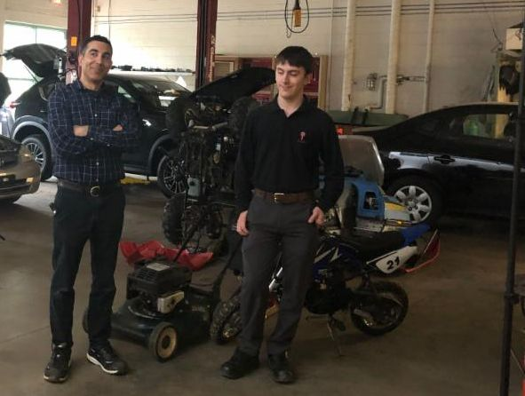 Male teacher standing with male student in the automotive classroom surround by small outdoor equipment and cars