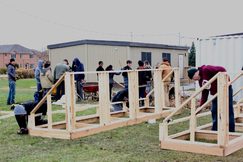 Students and adults building the micro-greenhouses