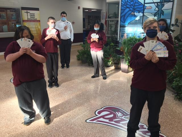 A group of students wearing masks and holding bookmarks that they have created to thank staff.