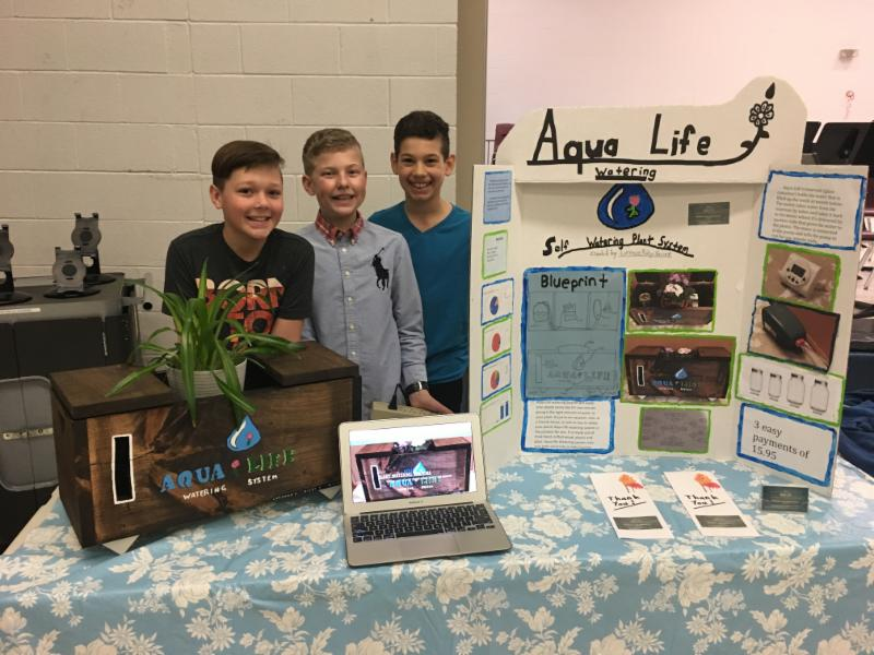 Three male students standing beside their invention display