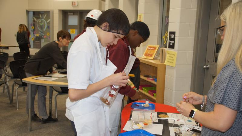 Two male students wearing aprons and hair nets making candy kabobs