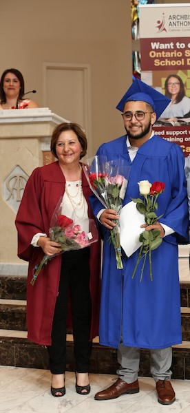 Female and male adults in graduation gowns and caps