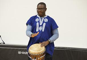 Male adult playing an African hand drum