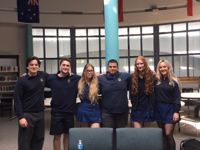 Male and female students standing for a photo in a school library