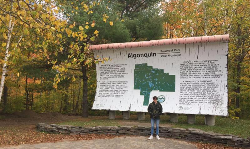Male student standing in front of Algonquin Park sign