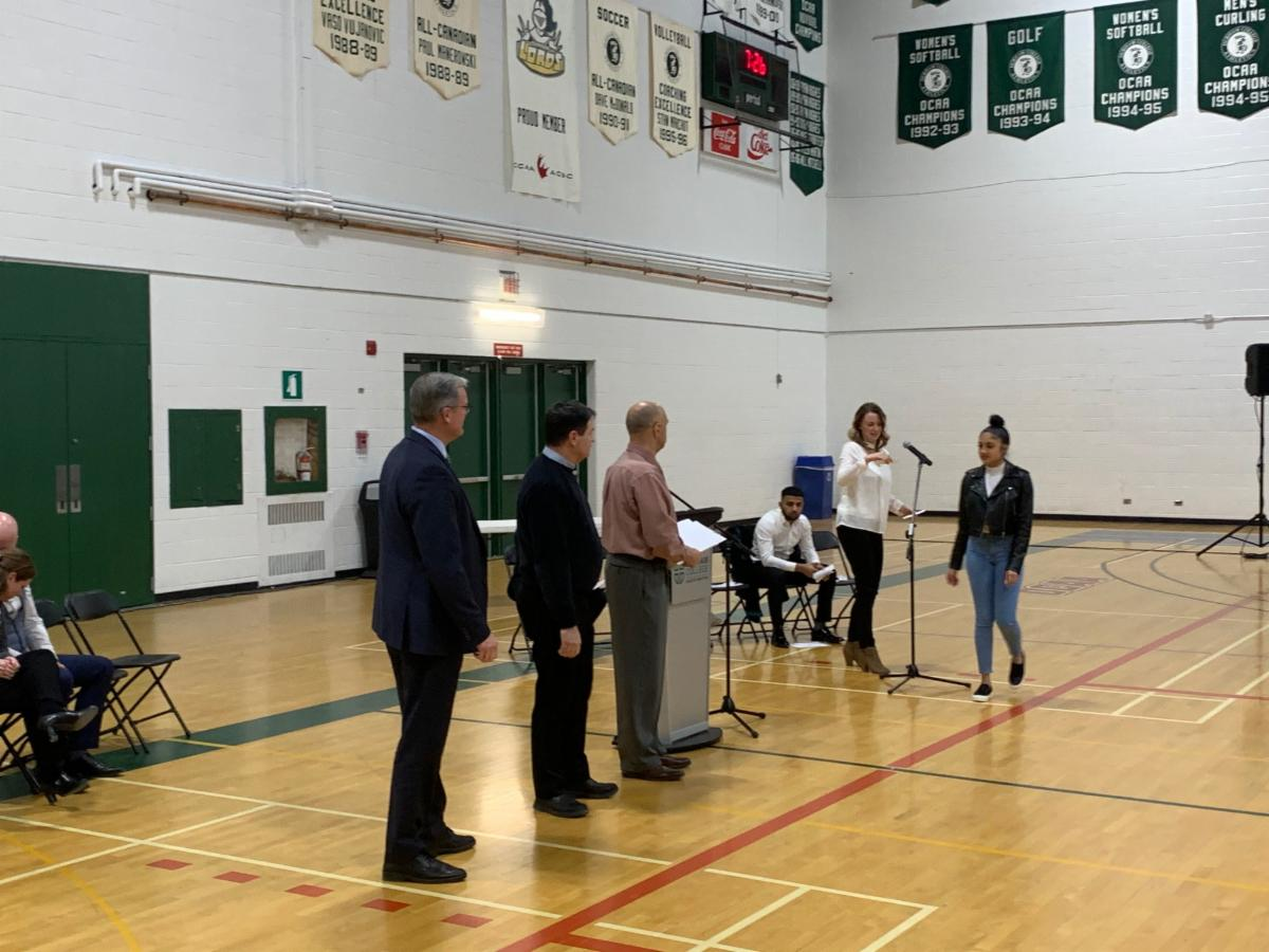 Female student receiving her Ontario Secondary School Diploma in a school's gym