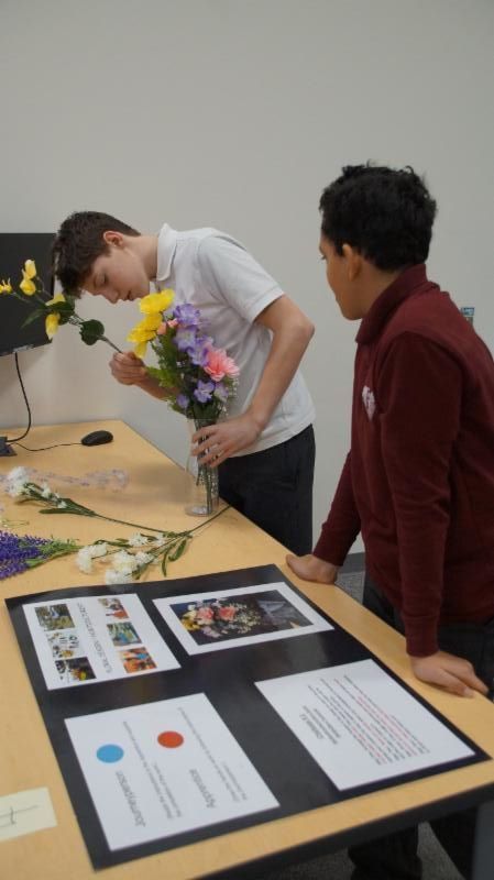 Two male students trying their hand at arranging flowers