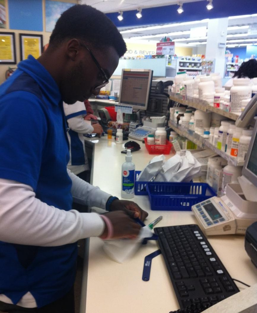 Male student working in a pharmacy as part of his cooperative education placement