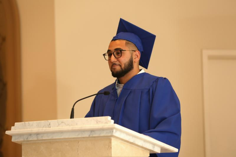Male student at a podium wearing a graduation gown and cap