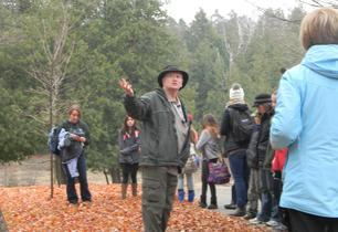 Adult male talking to students about trees during a walk in the forest