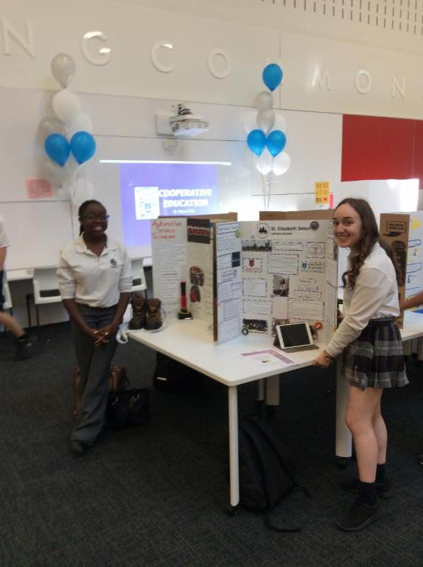 Two female student stand beside their display boards created on their co-operative education experience.