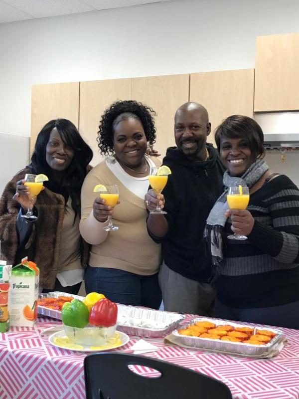 Male and female adults standing in front of food they prepared and holding orange juice in glasses