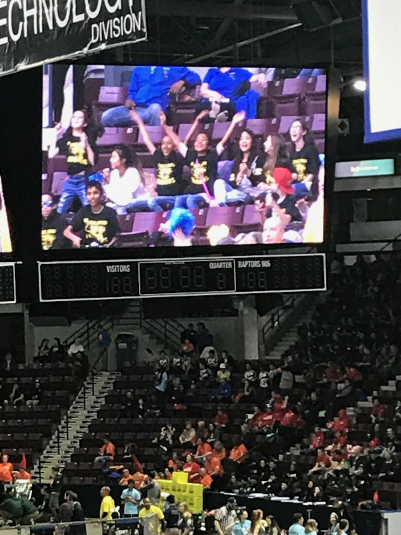 elementary students on the jumbo screen over the arena floor