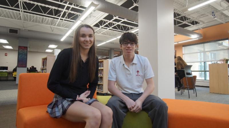 Female student wearing school uniform sitting with her exchange partner a male student from France
