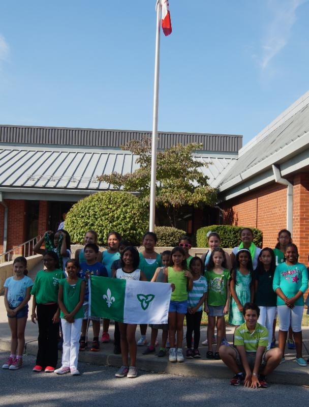 Group of male and female students wearing green and white and holding the Franco-Ontarian flag.