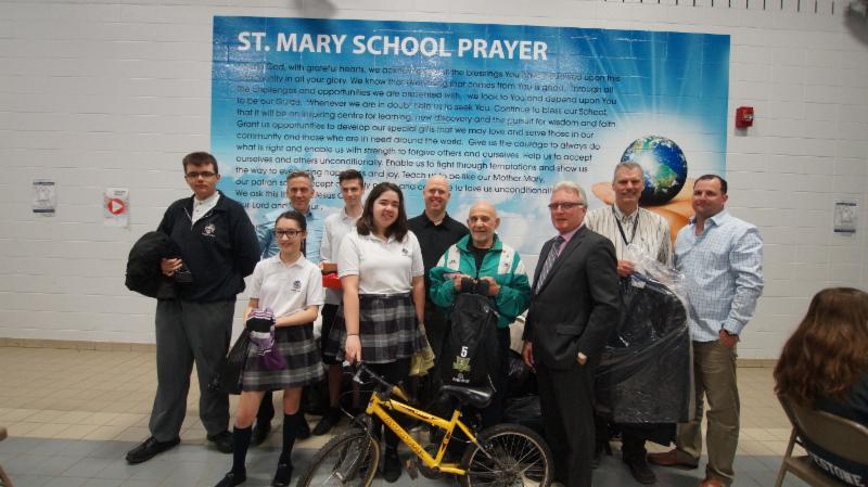 Students and adults holding clothing donations, a bike, shoes and a suit