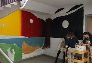 Three female student painting an Indigenous mural in the hallway of a secondary school.