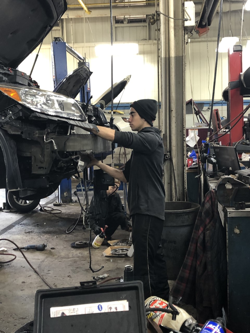 male student working on a car in an auto shop