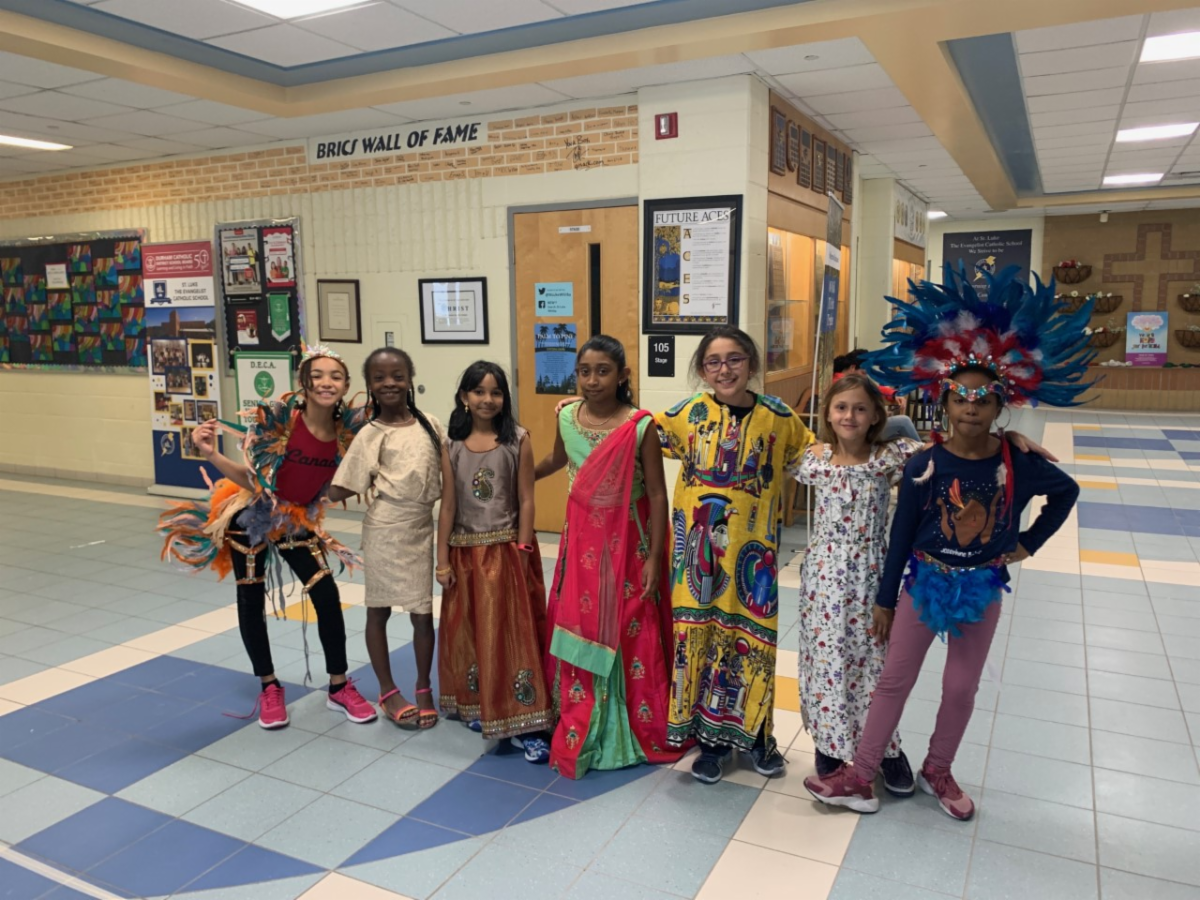 Eight female students dressed in traditional clothing representing their heritage.