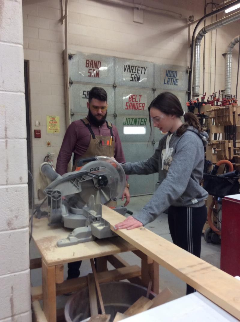 Female student using a saw in a woodworking classroom