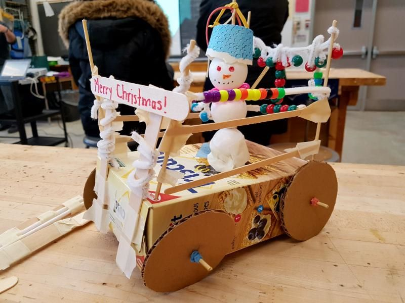 Cardboard car with snowman on top of it