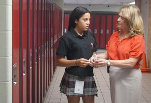 Female Principal helping female student open her combination lock for the first time.