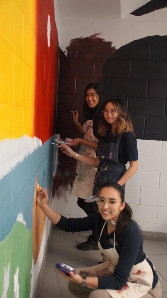 Three female students painting the Indigenous Education mural on the walls in a school's stairwell.