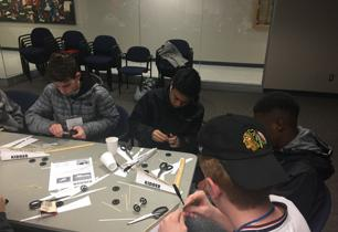 Male students work on building paper cars