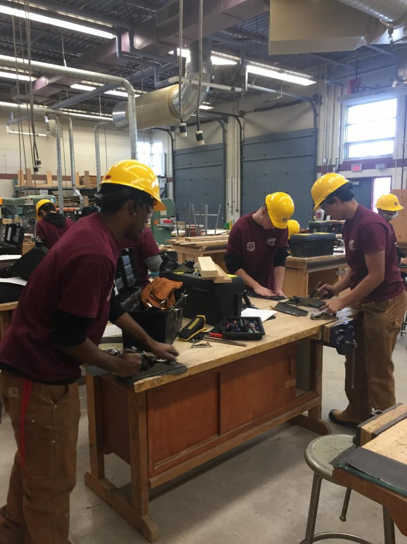 Three male students wearing yellow hard hats working in a woodshop classroom