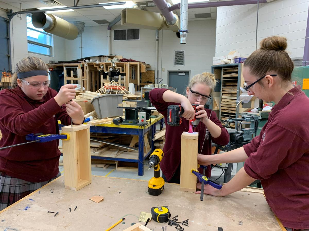 Female students in a woodworking shop building boxes