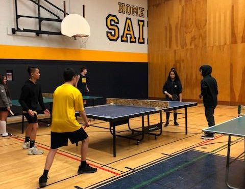Male and female students playing table tennis in a school gym