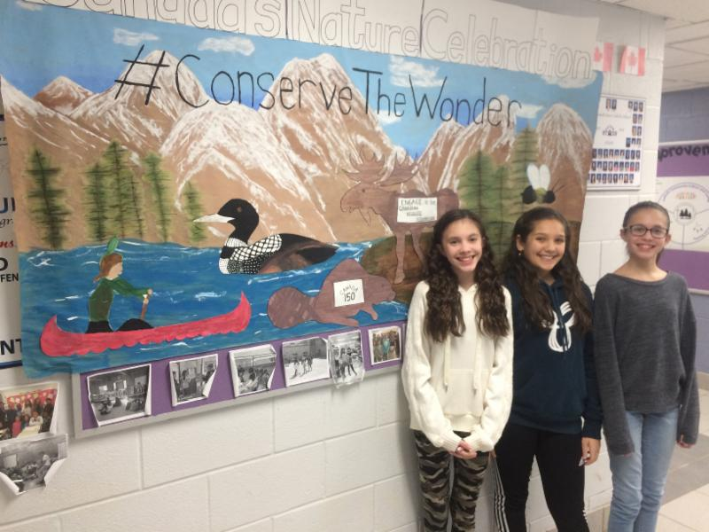 Three female student stand in front of a Conservation Mural in hallway