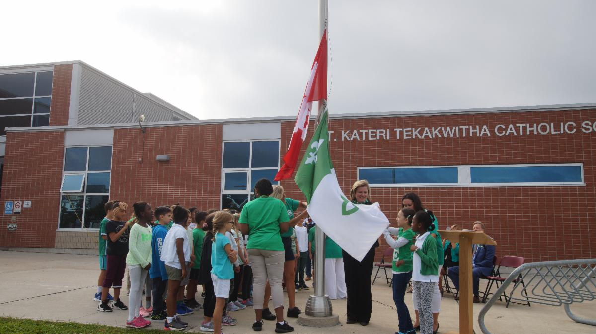 Students and staff raising the Franco-Ontario flag