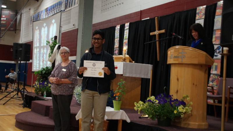 Male student holding certificate for his second place win for the essay winning contest