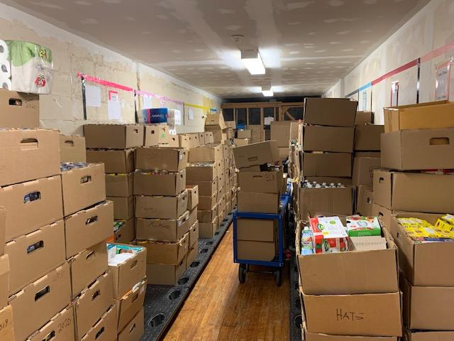 Boxes of food stored on top of boxes and on the floor in a storage room