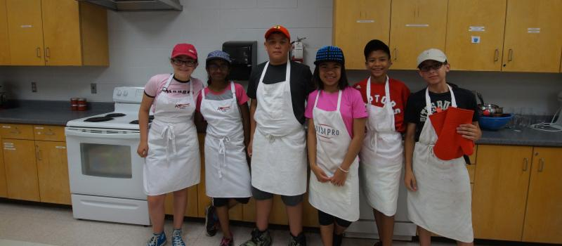Male and female students wearing aprons in a kitchen