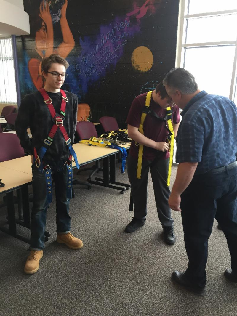 Students wearing safety harnesses for safety training