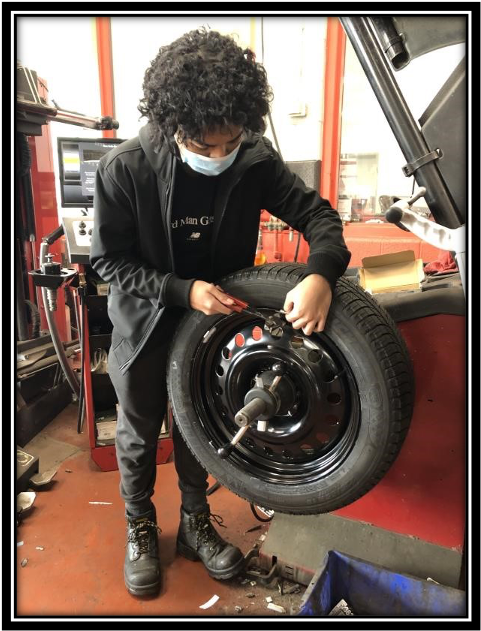 Student holding car tire